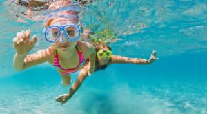 Young Mother With Child In Snorkeling Mask Dive In Coral Reef Se